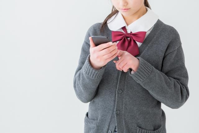 携帯電話を見る学生の写真